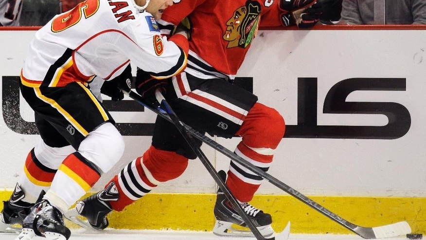 Chicago Blackhawks center Jonathan Toews (19) controls the puck against Calgary Flames defenseman Dennis Wideman (6) during the second period of an NHL hockey game in Chicago, Sunday, Dec. 14, 2014. (AP Photo/Nam Y. Huh)