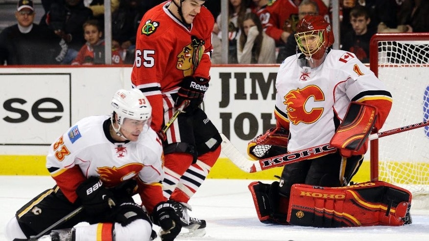Chicago Blackhawks center Andrew Shaw (65) battles for the puck against Calgary Flames defenseman Raphael Diaz (33) as Flames goalie Jonas Hiller (1) looks on during the second period of an NHL hockey game in Chicago, Sunday, Dec. 14, 2014. (AP Photo/Nam Y. Huh)