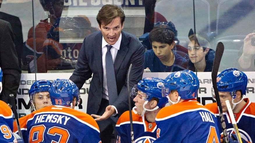 FILE - In this Sept. 24, 2013, file photo, Edmonton Oilers head coach Dallas Eakins talks to his players while playing the New York Rangers during third period NHL preseason hockey action in Edmonton, Alberta. Dallas Eakins has been fired as coach of the Edmonton Oilers, who have lost 15 of 16 games and are well on the way to missing the playoffs for the ninth consecutive season. According to reports, general manager Craig MacTavish will coach the team for the rest of the year. MacTavish is scheduled to speak with the media Monday, Dec. 15, 2014. (AP Photo/The Canadian Press, Jason Franson, File)