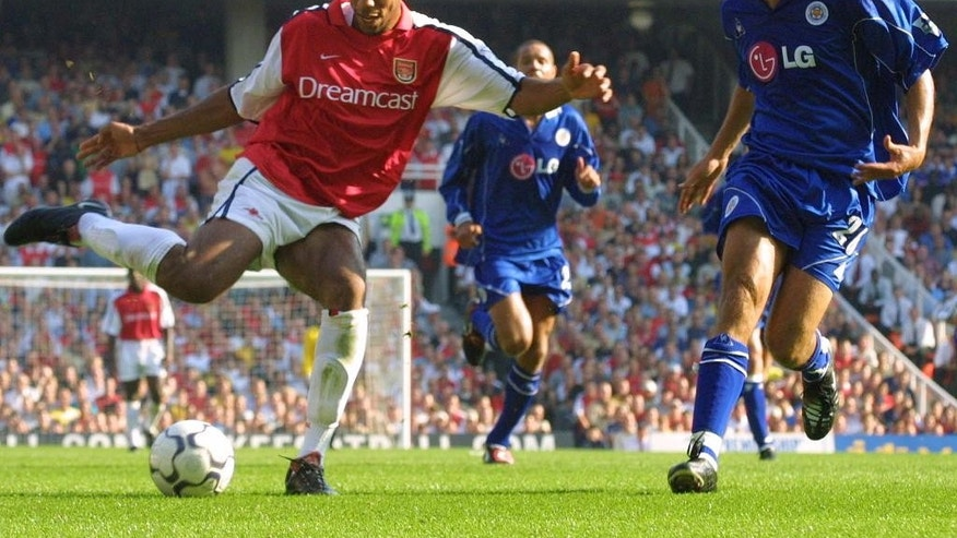FILE - In this Saturday, August 25, 2001 file photo Arsenal's Thierry Henry, left, fends off a challenge from an unidentified Leicester City player during their FA Premiership soccer match at Highbury in London. Thierry Henry has announced his retirement following a 20-year career. The 37-year-old Henry, a member of the France teams that won the 1998 World Cup and 2000 European Championship, will take up a media role as a consultant for Sky Sports channel.   (AP Photo/Dave Thomson, File)