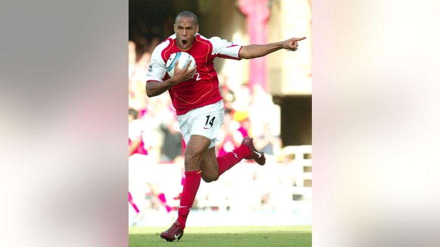 FILE - In this Sunday, Aug. 22, 2004 file photo Arsenal's Thierry Henry celebrates after team mate Dennis Bergkamp scored Arsenal's third goal during the Premiership game between Arsenal and Middlesbrough at Highbury, London.  Thierry Henry has announced his retirement following a 20-year career. The 37-year-old Henry, a member of the France teams that won the 1998 World Cup and 2000 European Championship, will take up a media role as a consultant for Sky Sports channel.   (AP Photo/John D McHugh, File)