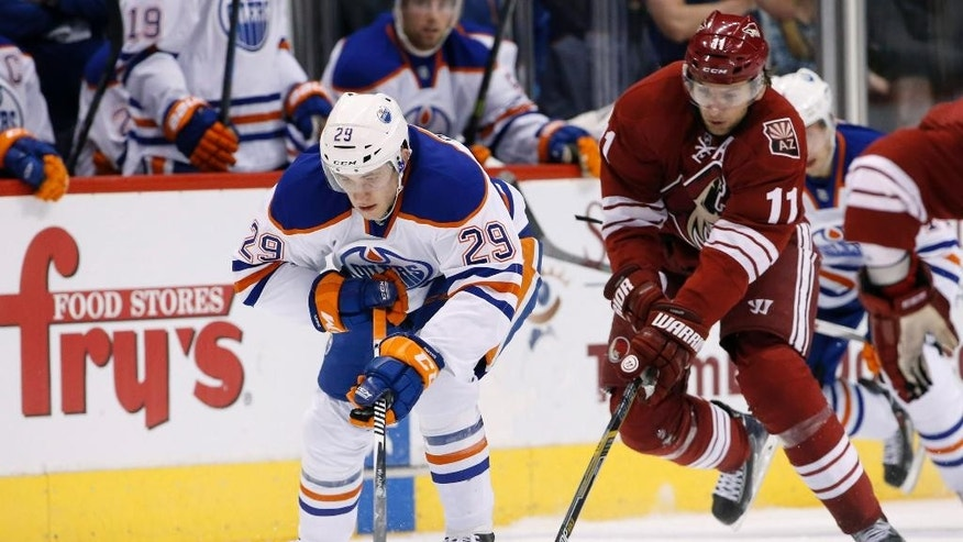 Edmonton Oilers' Leon Draisaitl (29) skates with the puck in front of Arizona Coyotes' Martin Hanzal (11), of the Czech Republic, during the first period of an NHL hockey game Tuesday, Dec. 16, 2014, in Glendale, Ariz. (AP Photo/Ross D. Franklin)