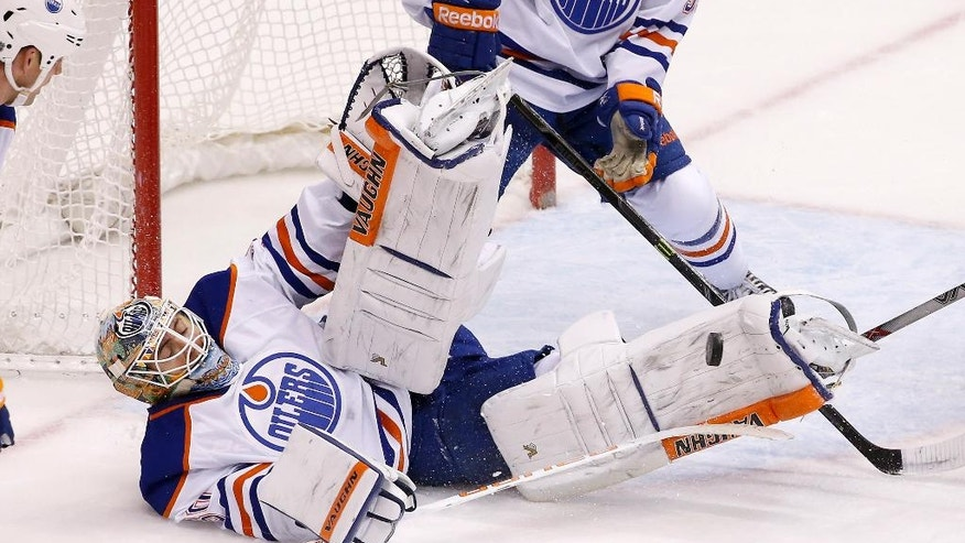Edmonton Oilers' Ben Scrivens makes a diving save on a shot by the Arizona Coyotes during the second period of an NHL hockey game Tuesday, Dec. 16, 2014, in Glendale, Ariz. (AP Photo/Ross D. Franklin)