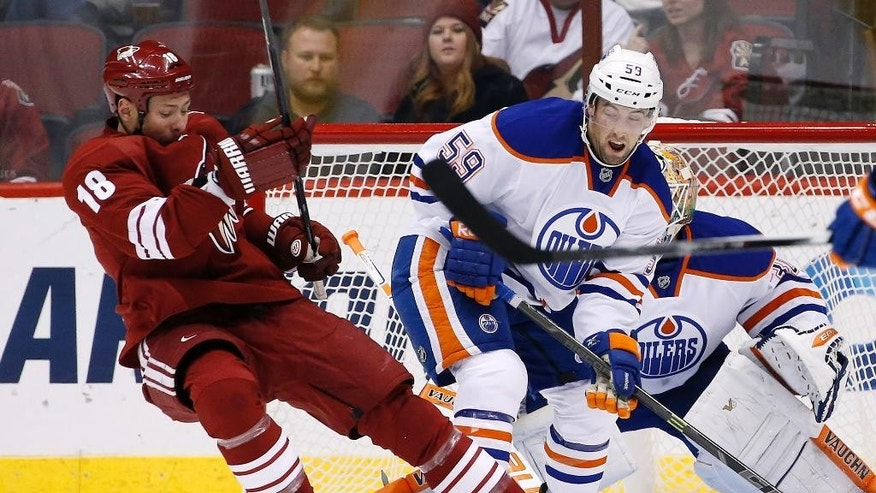 Arizona Coyotes' David Moss (18) creates interference in front of the goal as the puck gets blocked by Edmonton Oilers' Ben Scrivens, right, as Oilers' Brad Hunt (59) defends during the first period of an NHL hockey game Tuesday, Dec. 16, 2014, in Glendale, Ariz. (AP Photo/Ross D. Franklin)