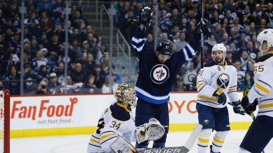 Winnipeg Jets' Michael Frolik (67) celebrates Mark Scheifele's first goal against Buffalo Sabres goaltender Michal Neuvirth (34) as Sabres' Andrej Meszaros (41) and Rasmus Ristolainen (55) watch during the second period of an NHL hockey game Tuesday, Dec. 16, 2014, in Winnipeg, Manitoba. (AP Photo/The Canadian Press, John Woods)