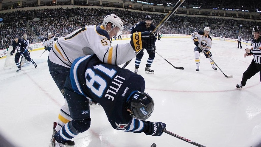 Buffalo Sabres' Tyler Myers (57) checks Winnipeg Jets' Bryan Little (18) deep in the corner during the second period of an NHL hockey game Tuesday, Dec. 16, 2014, in Winnipeg, Manitoba. (AP Photo/The Canadian Press, John Woods)