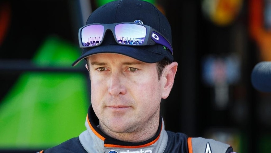 FILE - In this Oct. 9, 2014, file photo, Kurt Busch looks from the garage after practice for the NASCAR Bank of America Sprint Cup series auto race at Charlotte Motor Speedway in Concord, N.C. Busch's ex-girlfriend is delivering emotional testimony in a Delaware courtroom, seeking an order that Busch stay away from her following an alleged assault. Patricia Driscoll testified Tuesday, Dec. 16, 2014,  that Busch had choked her and smashed her head into a wall in September at Dover International Speedway. (AP Photo/Terry Renna, File)