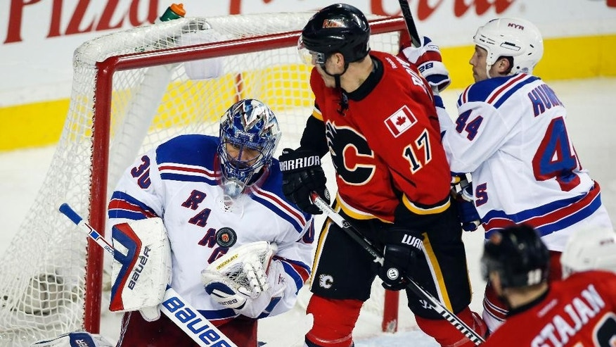 New York Rangers goalie Henrik Lundqvist, left, from Sweden, juggles the puck as Calgary Flames' Lance Bouma looks on during the third period of an NHL hockey game in Calgary, Alberta, Tuesday, Dec. 16, 2014. (AP Photo/The Canadian Press, Jeff McIntosh)