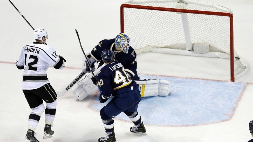 Los Angeles Kings' Marian Gaborik (12), of Slovakia, scores past St. Louis Blues goalie Jake Allen and Maxim Lapierre (40) during the second period of an NHL hockey game Tuesday, Dec. 16, 2014, in St. Louis. (AP Photo/Jeff Roberson)