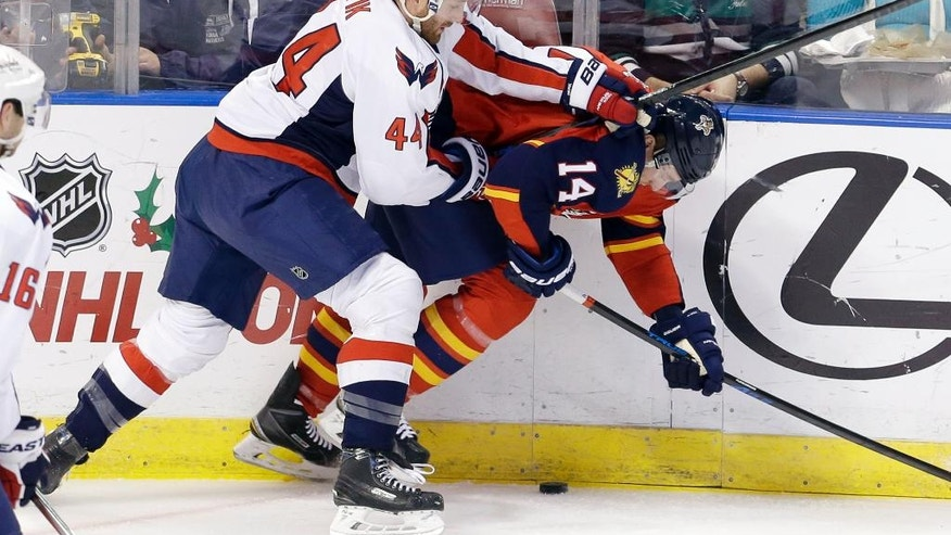 Washington Capitals defenseman Brooks Orpik (44) checks Florida Panthers left wing Tomas Fleischmann (14) during the first period of an NHL hockey game, in Sunrise, Fla., Tuesday, Dec. 16, 2014. (AP Photo/Alan Diaz)