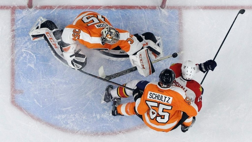Florida Panthers' Scottie Upshall, right, scores a goal past Philadelphia Flyers' Steve Mason, left, and Nick Schultz during the first period of an NHL hockey game, Thursday, Dec. 18, 2014, in Philadelphia. (AP Photo/Matt Slocum)