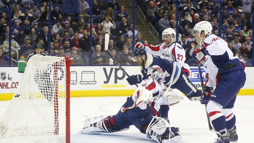 Columbus Blue Jackets' Nick Foligno (71) scores against Washington Capitals goalie Braden Holtby (70) in the second period of an NHL hockey game, Thursday, Dec. 18, 2014, in Columbus, Ohio. Capitals' Karl Alzner (27) and John Carlson (74) also defend. (AP Photo/Mike Munden)