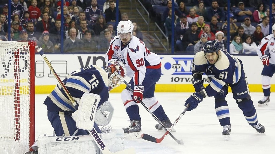 Columbus Blue Jackets goalie Sergei Bobrovsky (72) blocks a shot as Washington Capitals' Marcus Johansson (90) and Fedor Tyutin (51) close in during the first period of an NHL hockey game, Thursday, Dec. 18, 2014, in Columbus, Ohio. (AP Photo/Mike Munden)