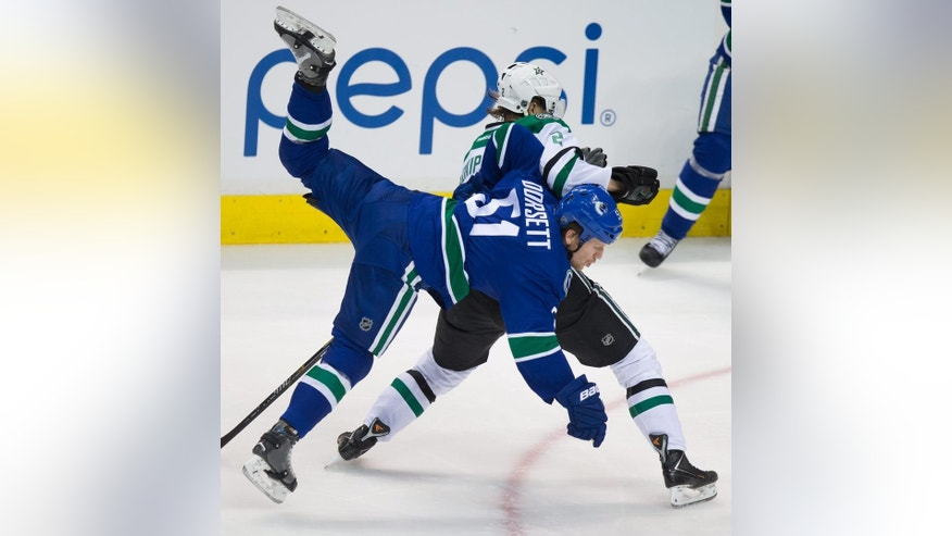 Vancouver Canucks' Derek Dorsett (51) and Dallas Stars' Jyrki Jokipakka, of Finland, collide during the second period of an NHL hockey game Wednesday, Dec. 17, 2014, in Vancouver, British Columbia. (AP Photo/The Canadian Press, Darryl Dyck)