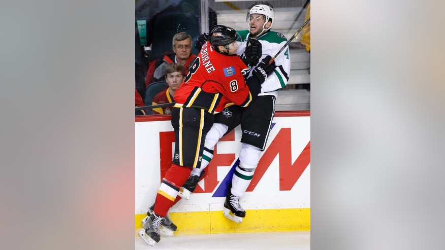 Dallas Stars' Jason Demers, right, takes a hit from Calgary Flames' Joe Colborne during the third period of an NHL hockey game Friday, Dec. 19, 2014, in Calgary, Alberta. (AP Photo/The Canadian Press, Larry MacDougal)
