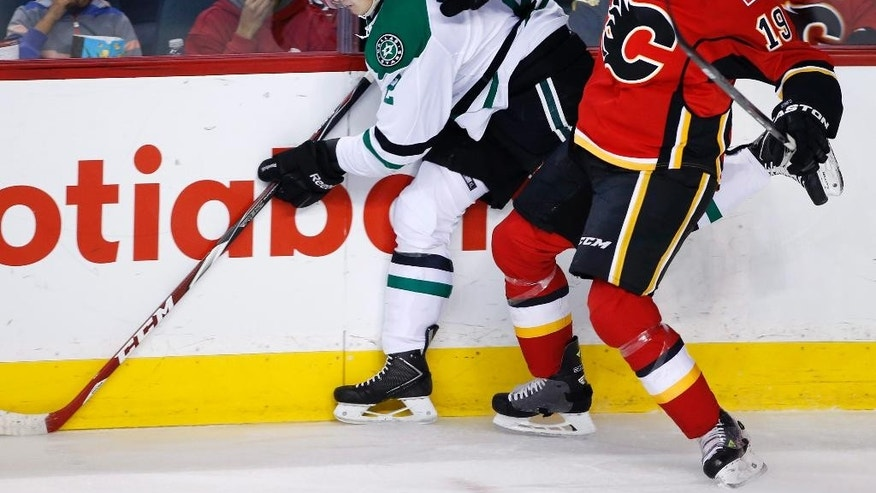 Dallas Stars' Jyrki Jokipakka, left, from Finland, is hit by Calgary Flames' David Jons during the first period of an NHL hockey game, Friday, Dec. 19, 2014 in Calgary, Alberta. (AP Photo/The Canadian Press, Larry MacDougal)