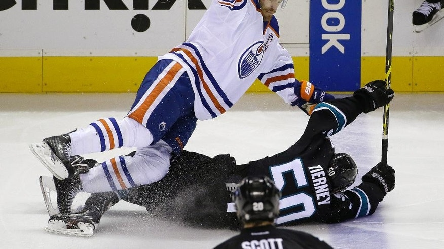 Edmonton Oilers defenseman Andrew Ference, top, tumbles over San Jose Sharks center Chris Tierney during the second period of an NHL hockey game Thursday, Dec. 18, 2014, in San Jose, Calif. Tierney was given a penalty on the play. (AP Photo/Eric Risberg)