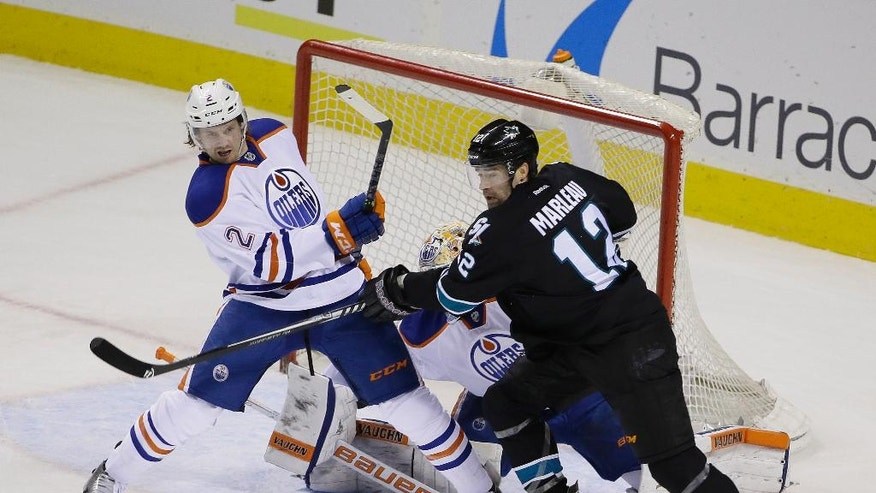 Edmonton Oilers defenseman Jeff Petry (2) and San Jose Sharks center Patrick Marleau (12) vie for the puck during the first period of an NHL hockey game Thursday, Dec. 18, 2014, in San Jose, Calif. (AP Photo/Eric Risberg)