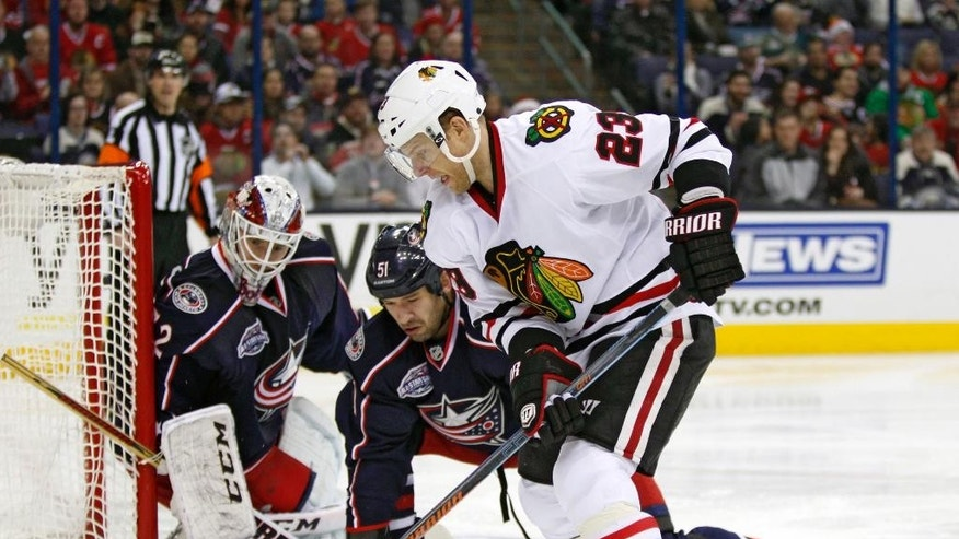 Chicago Blackhawks' Kris Versteeg (23) battles for the puck against Columbus Blue Jackets' Fedor Tyutin (51), of Russia, and goalie Sergei Bobrovosky (72), of Russia, during the first period of an NHL hockey game in Columbus, Ohio, Saturday, Dec. 20, 2014. (AP Photo/Paul Vernon)