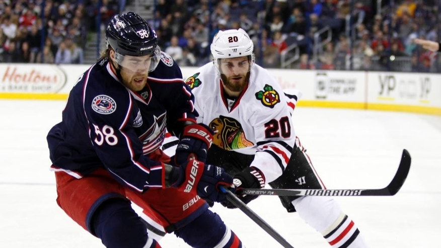 Columbus Blue Jackets' David Savard, left, works for the puck against Chicago Blackhawks' Brandon Saad during the first period of an NHL hockey game in Columbus, Ohio, Saturday, Dec. 20, 2014. (AP Photo/Paul Vernon)