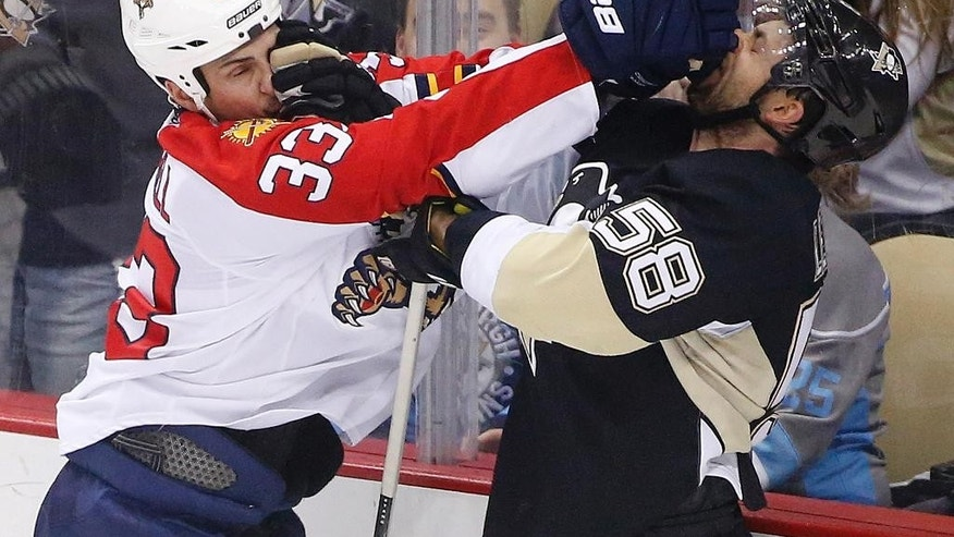 Pittsburgh Penguins' Kris Letang (58), and Florida Panthers' Willie Mitchell (33) each get a face full of glove during a fight in the first period of an NHL hockey game in Pittsburgh Saturday, Dec. 20, 2014. (AP Photo/Gene J. Puskar)