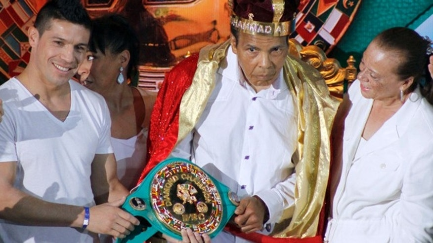 FILE - In this Monday, Dec. 3, 2012, file photo, the former heavyweight boxing champion Muhammad Ali, center, is crowned 'King of Boxing' while accompanied by his wife, Lonnie, right, and Argentine boxer Sergio Martinez during the 50th convention of the World Boxing Council in Cancun, Mexico. (AP Photo/Israel Leal, File)