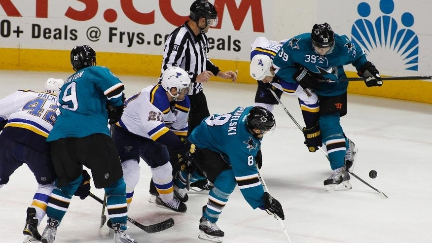 St. Louis Blues' Jay Bouwmeester, second from right, and San Jose Sharks' Logan Couture, right, struggle for the puck during the second period of an NHL hockey game, Saturday, Dec. 20, 2014, in San Jose, Calif. (AP Photo/George Nikitin)
