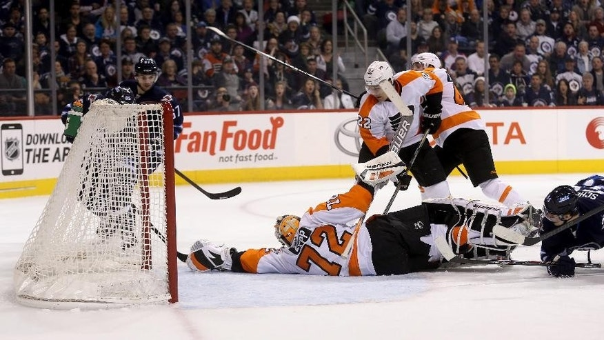 Winnipeg Jets' Mathieu Perreault (85), left, beats an outstretched Philadelphia Flyers goaltender Rob Zepp (72) to score during the second period of an NHL hockey game, Sunday, Dec. 21, 2014 in Winnipeg, Manitoba. (AP Photo/The Canadian Press, Trevor Hagan)