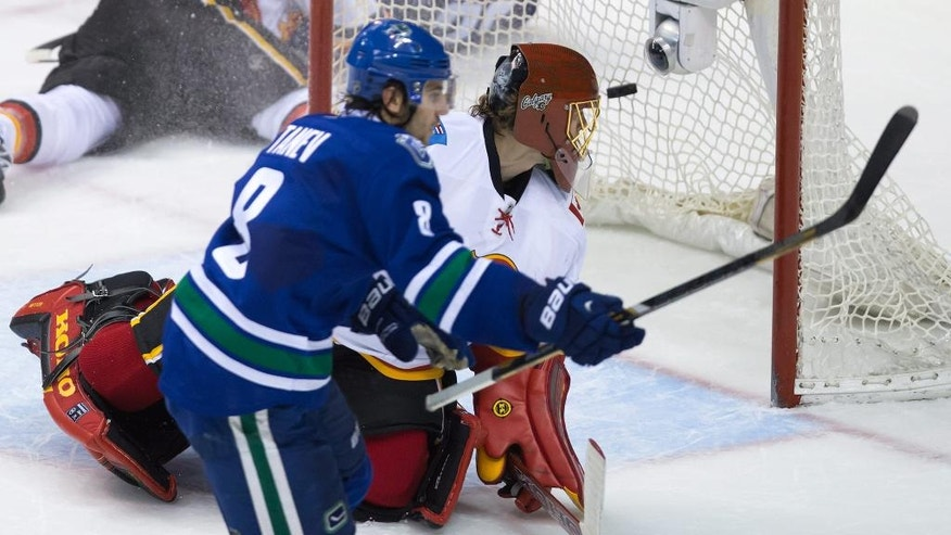 Vancouver Canucks' Chris Tanev, left, scores the winning goal against Calgary Flames' goalie Jonas Hiller, of Sweden, during the overtime period of an NHL hockey game in Vancouver, British Columbia, on Saturday, Dec. 20, 2014. (AP Photo/The Canadian Press, Darryl Dyck)