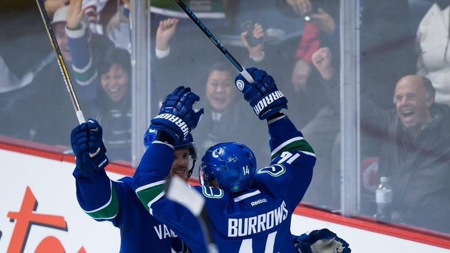 Vancouver Canucks' Daniel Sedin, of Sweden, and Alex Burrows celebrate Burrows' second goal against the Arizona Coyotes during second period NHL hockey action in Vancouver, British Columbia on Monday, Dec. 22, 2014. (AP Photo/The Canadian Press, Darryl Dyck)