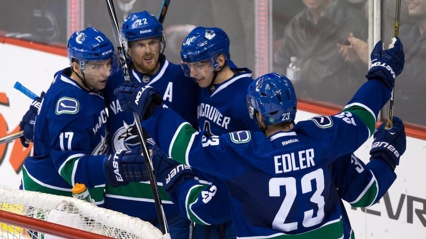 Vancouver Canucks' Radim Vrbata, of the Czech Republic,, from left to right, Daniel Sedin, of Sweden, Alex Burrows, Henrik Sedin, hidden, of Sweden, and Alexander Edler, of Sweden, celebrate Burrows' second goal against the Arizona Coyotes during second period NHL hockey action in Vancouver, British Columbia on Monday, Dec. 22, 2014. (AP Photo/The Canadian Press, Darryl Dyck)