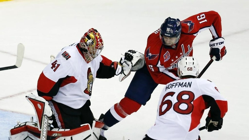 Washington Capitals right wing Eric Fehr (16) goes for the puck as it bounces off the pads of Ottawa Senators goalie Craig Anderson (41) with left wing Mike Hoffman (68) nearby, in the third period of an NHL hockey game, Monday, Dec. 22, 2014, in Washington. The Capitals won 2-1. (AP Photo/Alex Brandon)