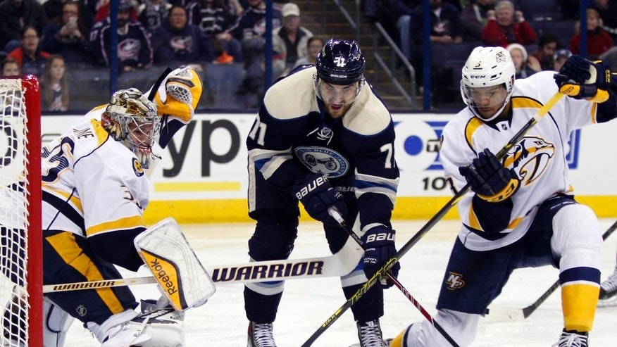Columbus Blue Jackets' Nick Foligno (71) works for the puck between Nashville Predators goalie Pekka Rinne (35), of Finland, and Seth Jones (3) during second period of an NHL hockey game in Columbus, Ohio, Monday, Dec. 22, 2014. (AP Photo/Paul Vernon)