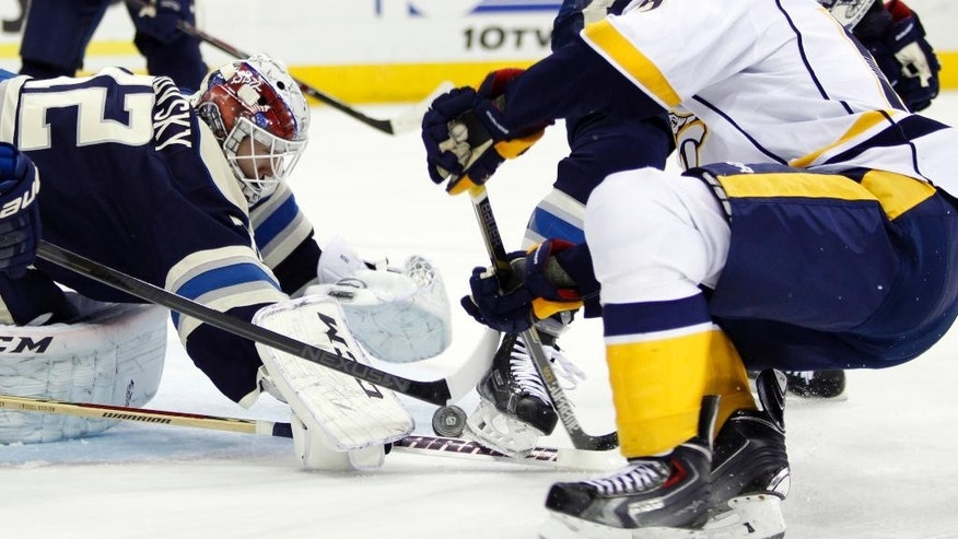 Columbus Blue Jackets goalie Sergei Bobrovosky, left, of Russia, makes a stop in front of Nashville Predators' Craig Smith during first period of an NHL hockey game in Columbus, Ohio, Monday, Dec. 22, 2014. (AP Photo/Paul Vernon)