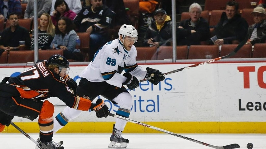 Anaheim Ducks Hampus Lindholm gets the puck away from San Jose Sharks left wing Barclay Goodrow during the first period of an NHL hockey game Monday, Dec. 22, 2014, in Anaheim, Calif. (AP Photo/Lenny Ignelzi)