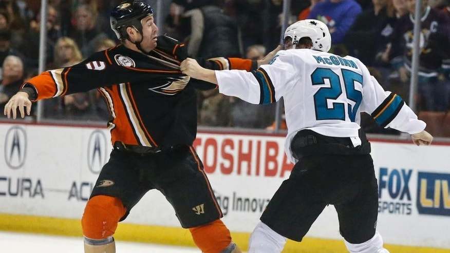 Anaheim Ducks defenseman Clayton Stoner, left, and San Jose Sharks left wing Tye McGinn fight during the first period of an NHL hockey game Monday, Dec. 22, 2014, in Anaheim, Calif. (AP Photo/Lenny Ignelzi)
