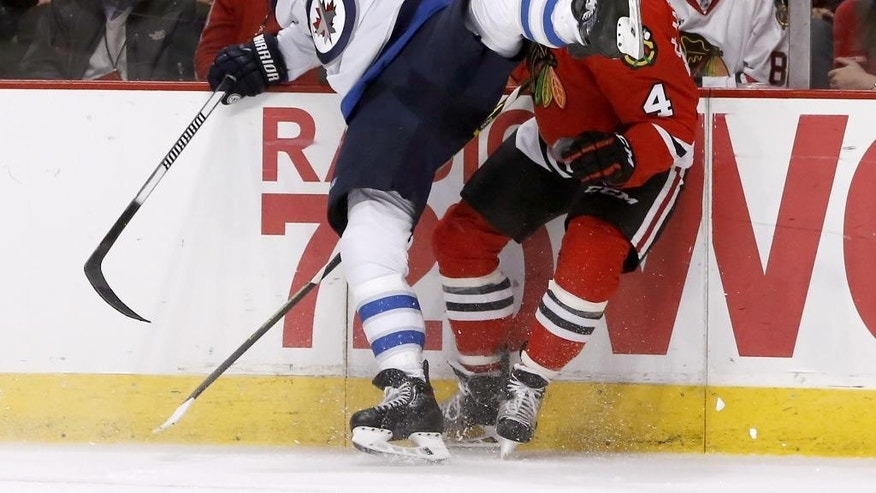 Winnipeg Jets left wing Andrew Ladd (16) and Chicago Blackhawks defenseman Niklas Hjalmarsson (4) collide along the boards during the first period of an NHL hockey game Tuesday, Dec. 23, 2014, in Chicago. (AP Photo/Charles Rex Arbogast)