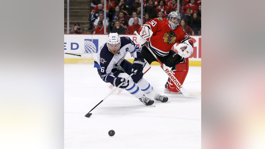 Winnipeg Jets right wing Blake Wheeler (26) chases a puck after Chicago Blackhawks goalie Corey Crawford cleared it from in front of the net during the first period of an NHL hockey game Tuesday, Dec. 23, 2014, in Chicago. (AP Photo/Charles Rex Arbogast)