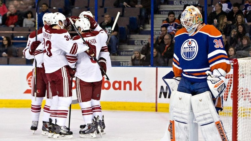 Arizona Coyotes teammates celebrate a goal on Edmonton Oilers goalie Ben Scrivens (30) during the first period of an NHL hockey game in Edmonton, Alberta, Tuesday, Dec. 23, 2014. (AP Photo/The Canadian Press, Jason Franson)