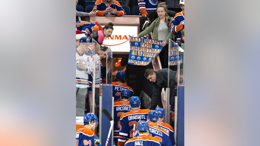 An Edmonton Oilers fan hangs a sign over the Oilers players as they leave the ice after losing to the Arizona Coyotes in an NHL hockey game in Edmonton, Alberta, Tuesday, Dec. 23, 2014. The Coyotes won 5-1. (AP Photo/The Canadian Press, Jason Franson)