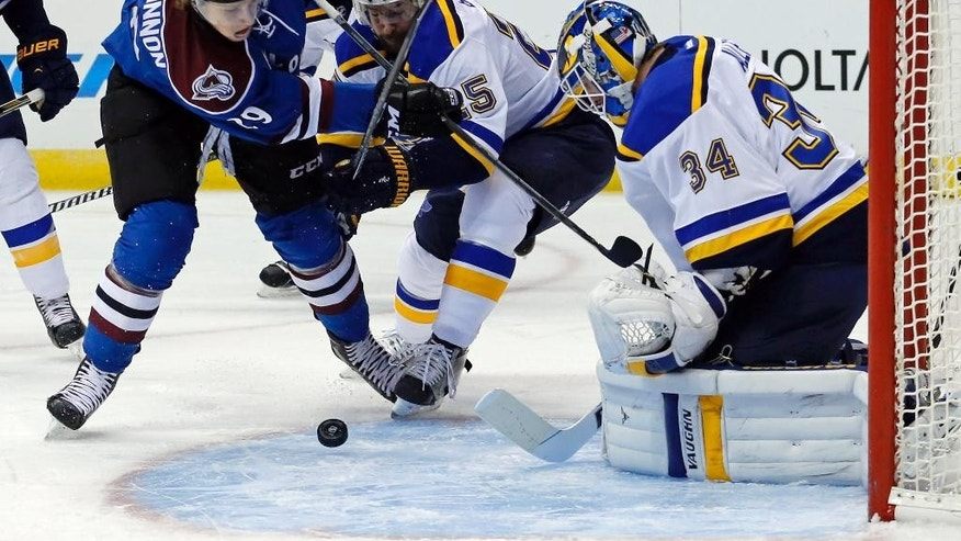 St. Louis Blues goalie Jake Allen (34) blocks a shot by Colorado Avalanche center Nathan MacKinnon (29) as Blues' Chris Butler (25) defends during the first period of an NHL hockey game Tuesday, Dec. 23, 2014, in Denver. (AP Photo/Jack Dempsey)