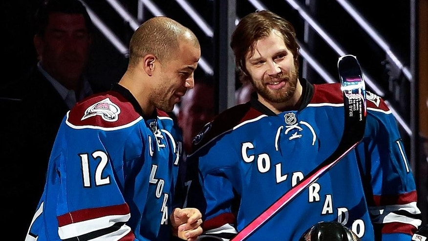 Colorado Avalanche right wing Jarome Iginla (12) presents Brad Stuart with a silver stick to commemorate Stuart's 1,000the career NHL hockey game, before the Avalanche played the St. Louis Blues on Tuesday, Dec. 23, 2014, in Denver. (AP Photo/Jack Dempsey)