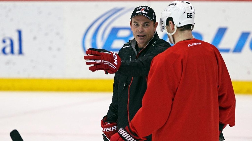New Jersey Devils coach Adam Oates talks with right wing Jaromir Jagr (68) during NHL hockey practice on Saturday, Dec. 27, 2014, in Newark, N.J. Devils are replacing the fired Pete DeBoer with a three-headed coaching staff. Former Washington Capitals coach Oates, ex-Devils assistant and star defenseman Scott Stevens and general manager Lou Lamoriello will split duties on the bench. (AP Photo/Adam Hunger)