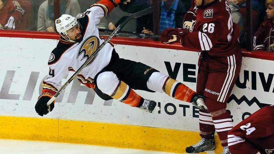 Arizona Coyotes defenseman Michael Stone (26) checks Anaheim Ducks center Nate Thompson (44) in the first period during an NHL hockey game, Saturday, Dec. 27, 2014, in Glendale, Ariz. (AP Photo/Rick Scuteri)