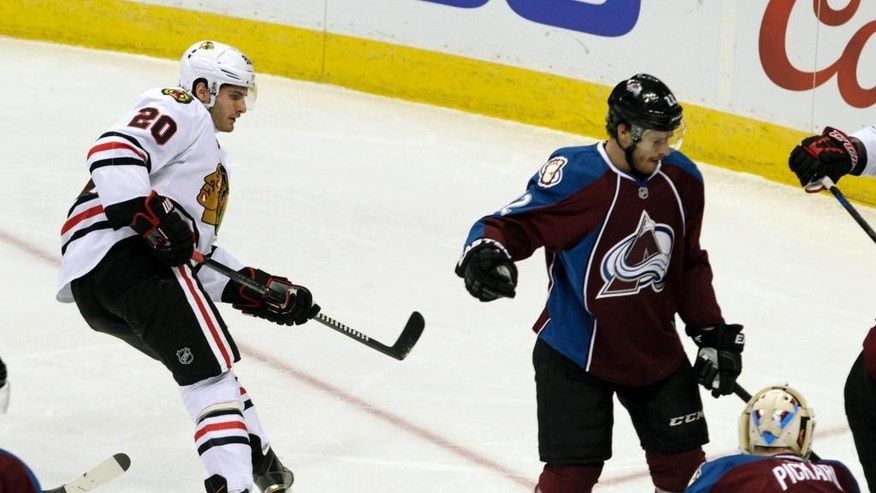 Chicago Blackhawks left wing Brandon Saad (20) watches his shot go past Colorado Avalanche defenseman Zach Redmond (22) and Avalanche goalie Calvin Pickard (31) for a goal in the first period of an NHL hockey game in Denver, Saturday, Dec. 27, 2014.(AP Photo/Joe Mahoney)