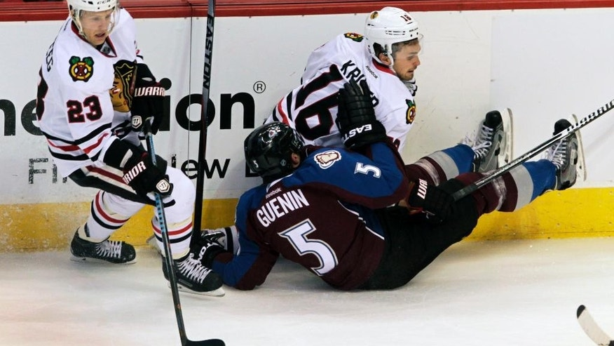 Chicago Blackhawks right wing Kris Versteeg (23) takes the puck around a collision between Blackhawks center Marcus Kruger (16) and Colorado Avalanche defenseman Nate Guenin (5) in the first period of  an NHL game in Denver, Saturday, Dec. 27, 2014.(AP Photo/Joe Mahoney)