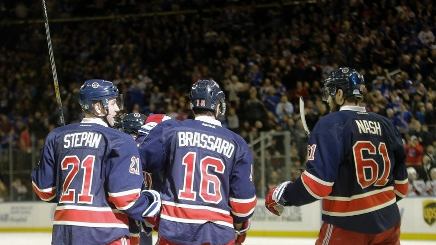 New York Rangers' Derek Stepan (21) celebrates with teammates Derick Brassard (16) and Rick Nash (61) after scoring a goal during the second period of an NHL hockey game against the New Jersey Devils Saturday, Dec. 27, 2014, in New York. (AP Photo/Frank Franklin II)