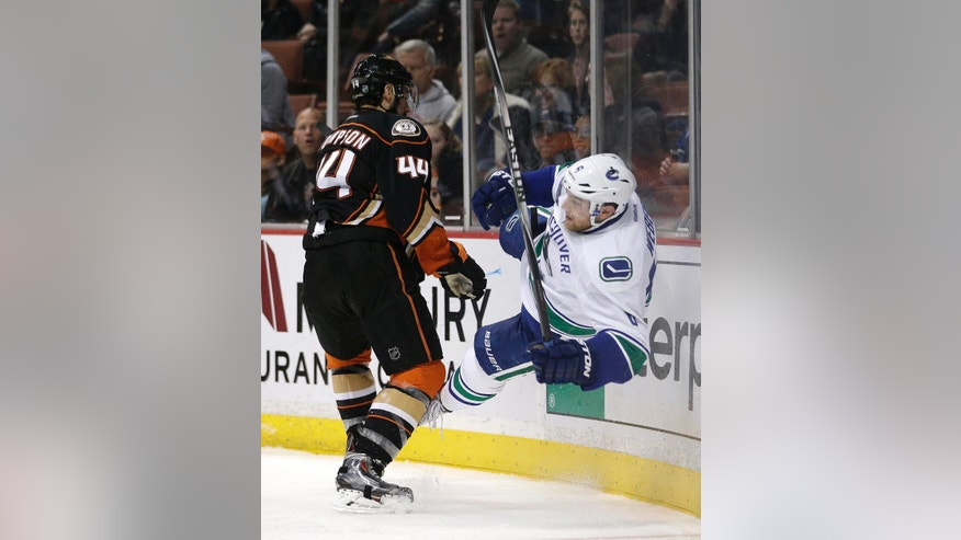 Anaheim Ducks' Nate Thompson, left, checks Vancouver Canucks' Yannick Weber, of Switzerland, during the second period of an NHL hockey game Sunday, Dec. 28, 2014, in Anaheim, Calif. (AP Photo/Jae C. Hong)