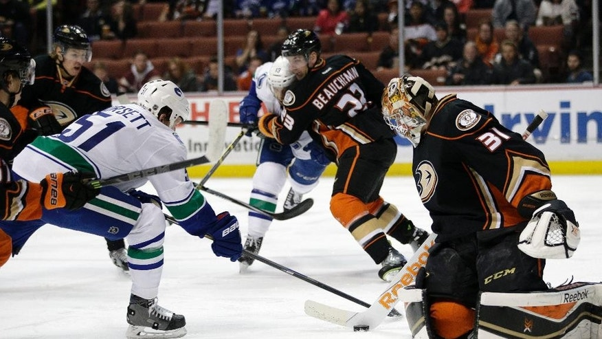 Anaheim Ducks goalie Frederik Andersen, right, of Denmark, stops a shot in front of Vancouver Canucks' Derek Dorsett during the first period of an NHL hockey game Sunday, Dec. 28, 2014, in Anaheim, Calif. (AP Photo/Jae C. Hong)