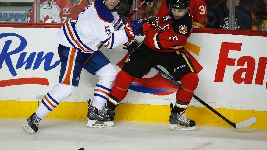 Edmonton Oilers' Mark Fayne, left, pushes Calgary Flames' Mark Giordano away from the puck during the third period of an NHL hockey game Saturday, Dec. 27, 2014, in Calgary, Alberta. (AP Photo/The Canadian Press, Jeff McIntosh)